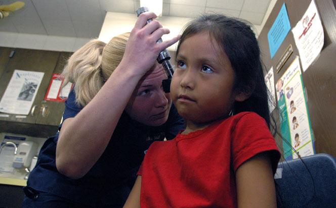 Nursing student examining young girl