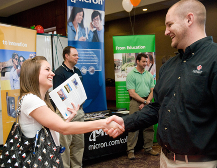 Student and career fair presenter shaking hands