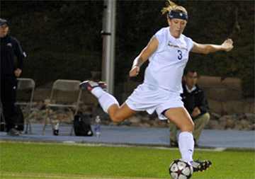Kristi Anreasses kicking a soccer ball
