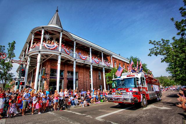 A flag cobered firetruck progresses through the parade