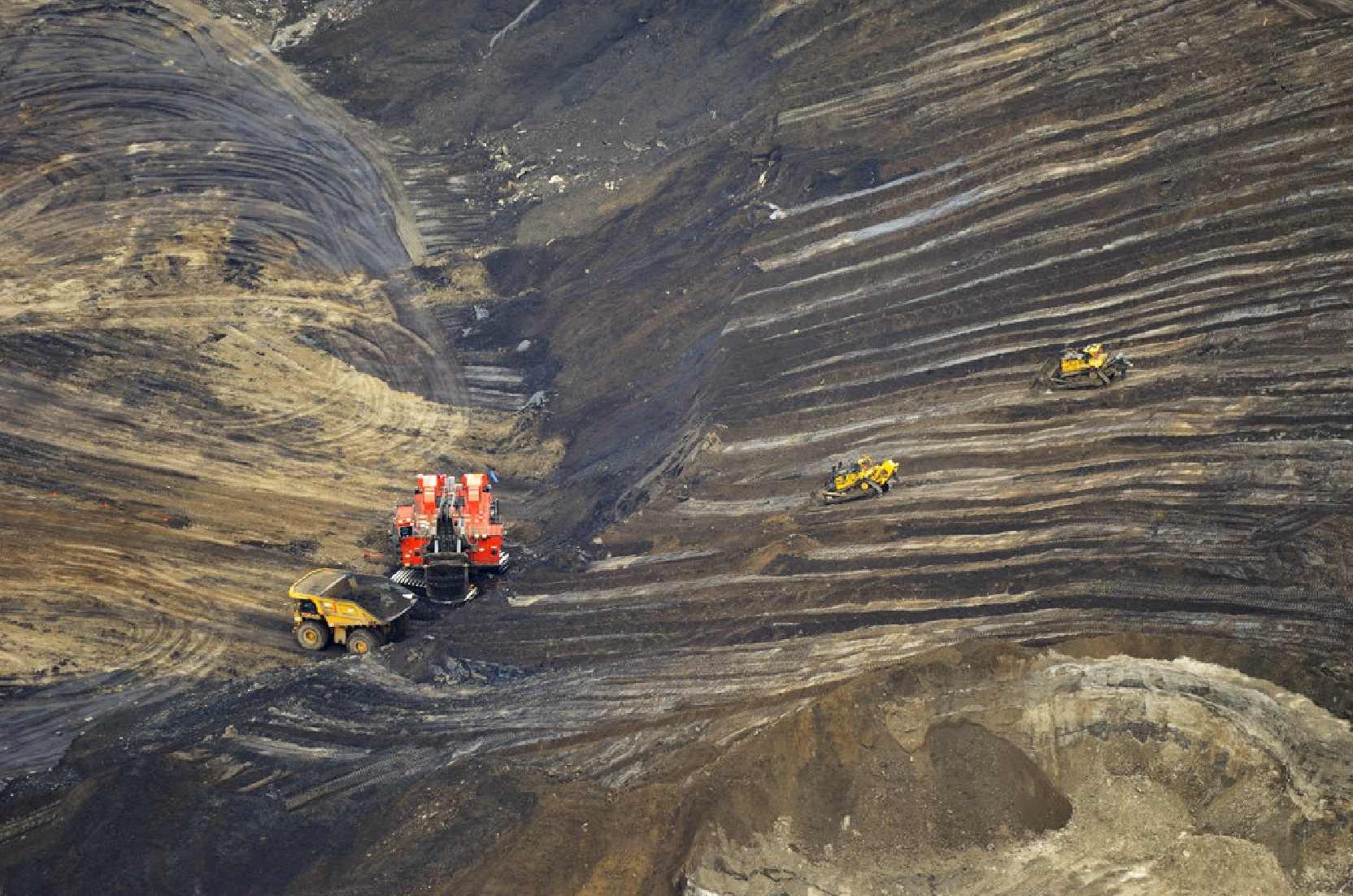 Bulldozers and trucks at the bottom of the oil sands
