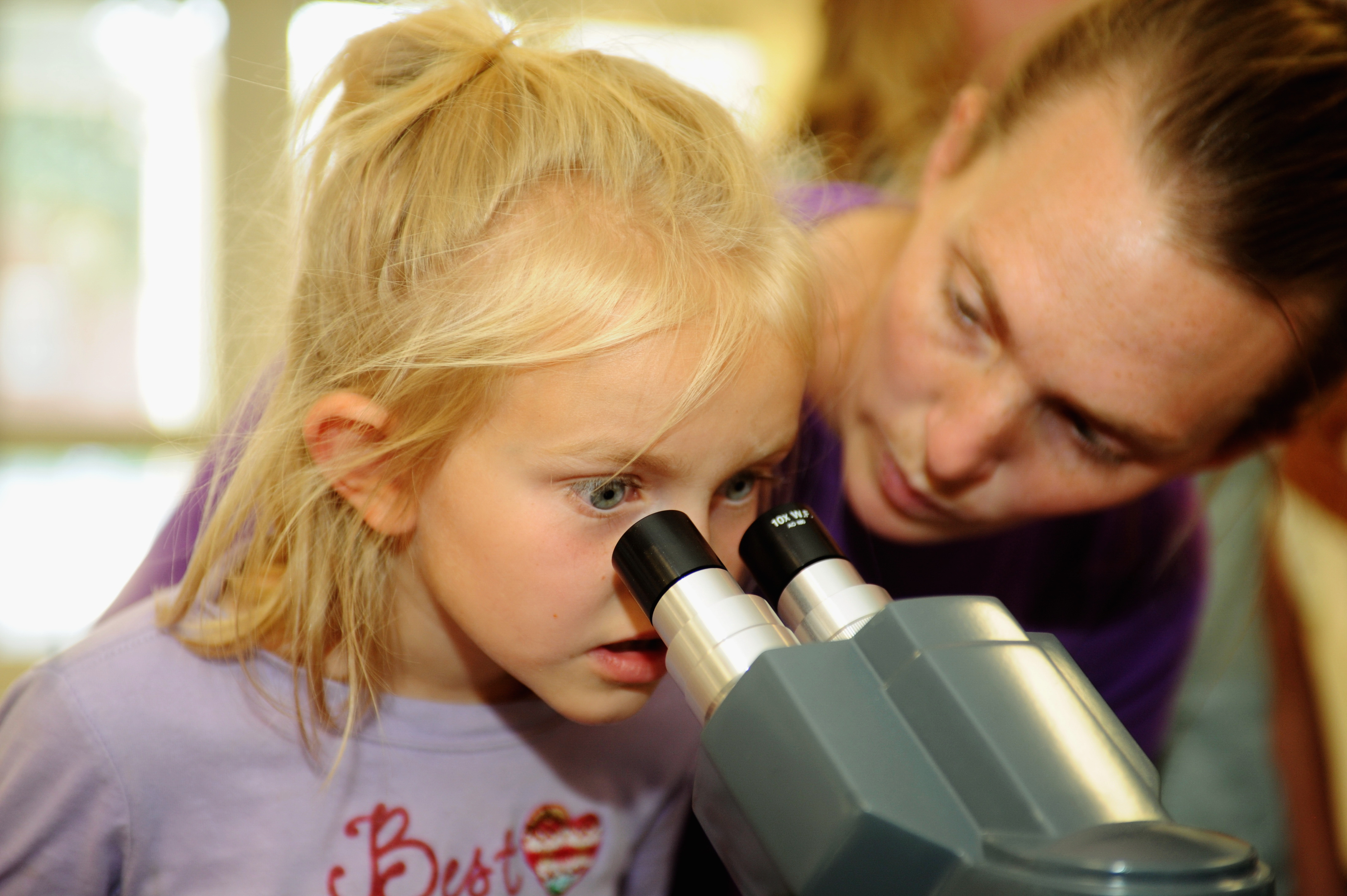 Young girl peering into a microscope
