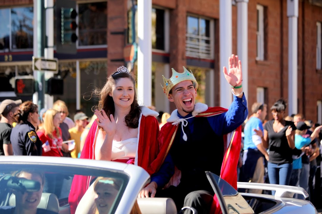 Homecoming king and queen wave in the parade