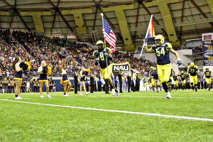 Players hold flags as the NAU football team takes the field