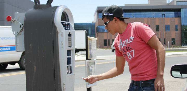 student uses a parking ticket machine