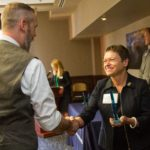 NAU President Rita Cheng smiles and shakes the hand of Tim Darby