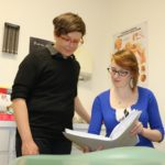 Kevin Shaw and Breanna West read a large file in a clinic office