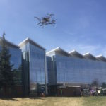 A small drone hovers in front of the engineering building