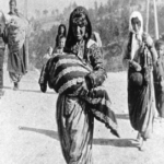 A woman walks amongst others, holding a baby