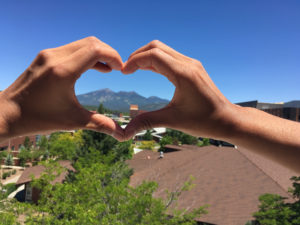 Hands in heart shape around mountains