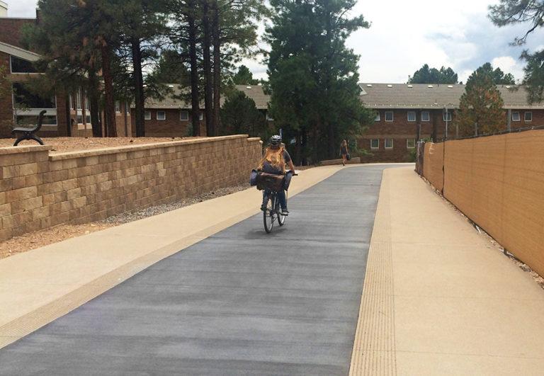 New pedway design featuring a dark gray concrete bike lane running between two lighter gray pedestrian pathways.