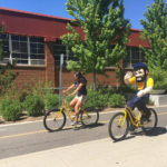 Girl and Louie riding yellow bikes on pedway