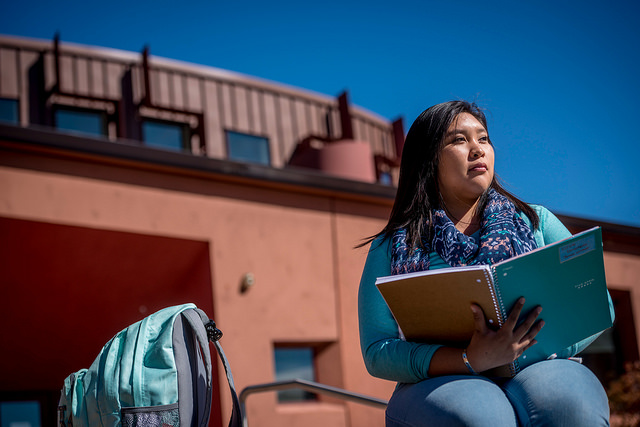 An NAU student studies outside of the Native American Cultural Center.