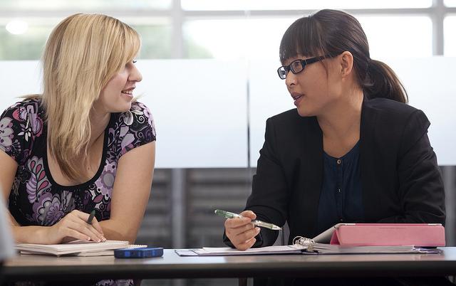 Women discuss notes.