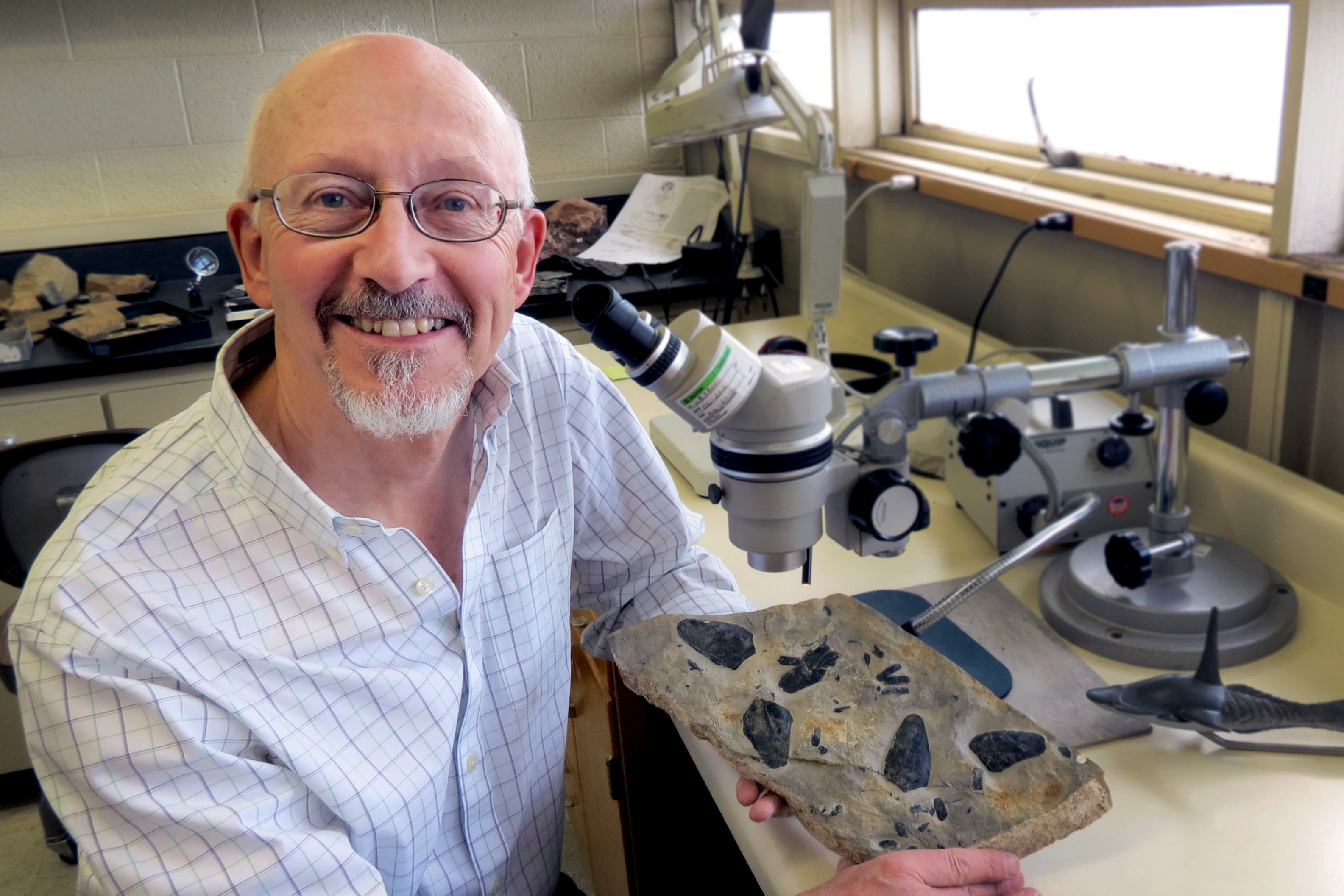 D.K.Elliott in lab with fossil heterostracans