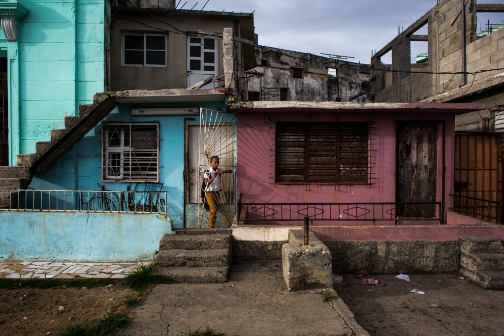 A schoolboy stands on a proch just after sunrise in Havana, Cuba.