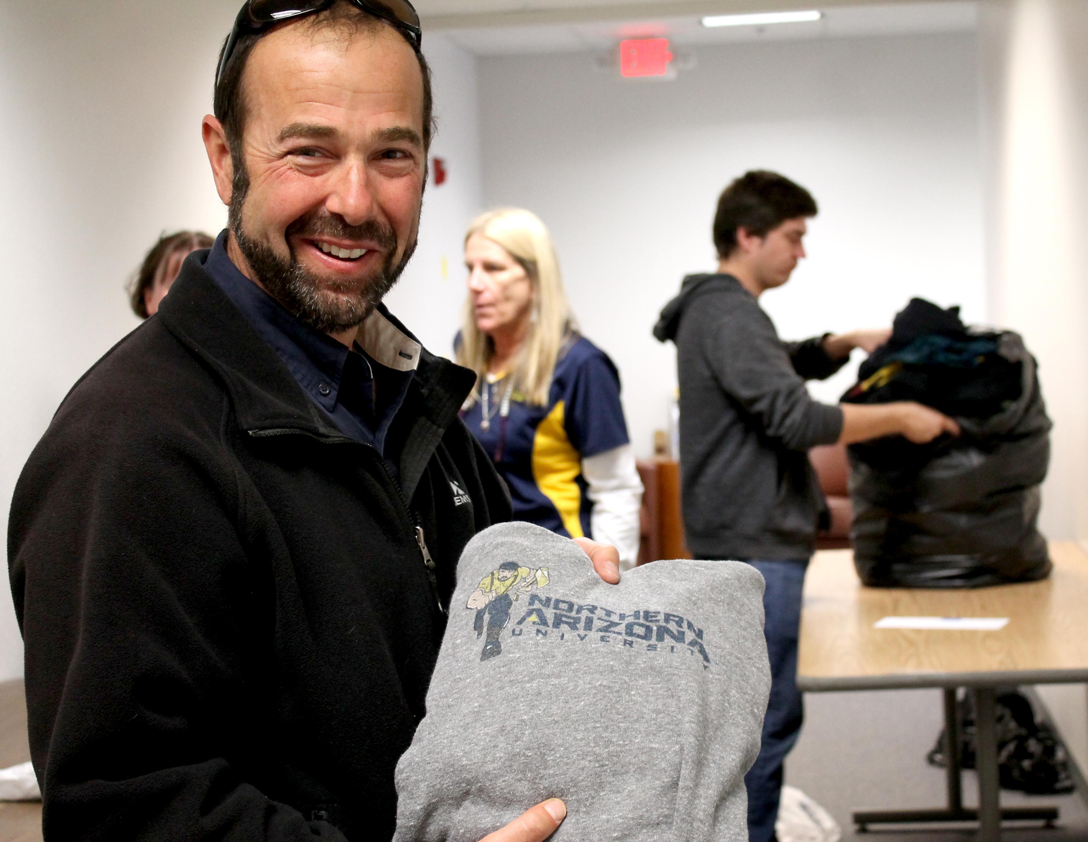 Scott Halle holds up donated NAU shirt