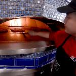 DuB worker prepares pizza in oven