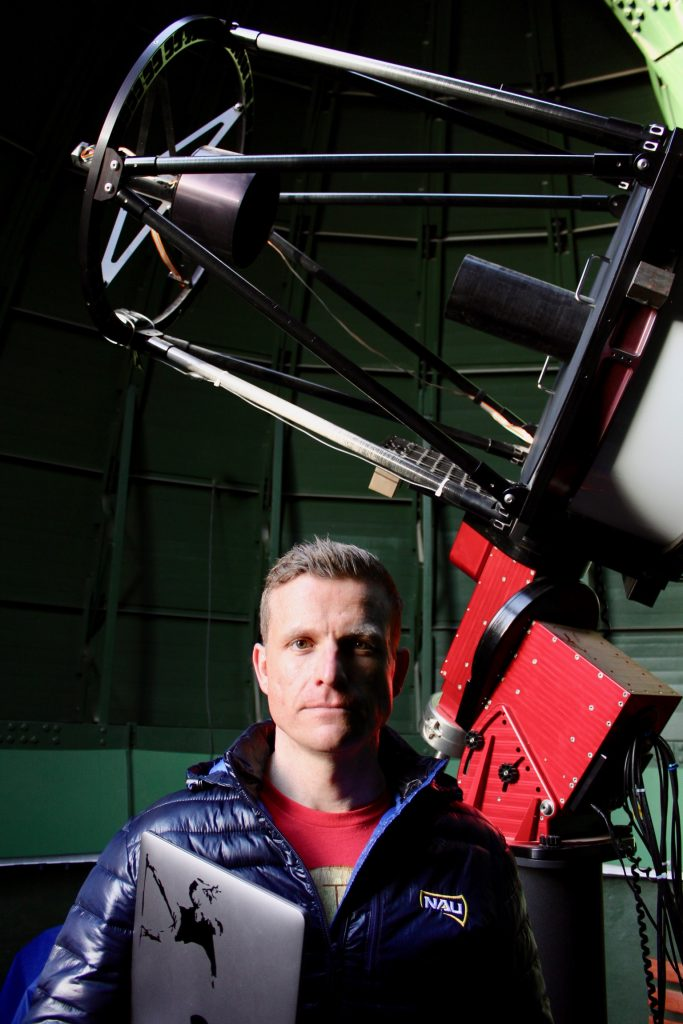 Colin Chandler stands in front of a telescope.