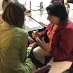 CUPI member Hannah Roberts speaks with NAIC leader Maria de Jesus Guillen at an NAIC immigration team meeting