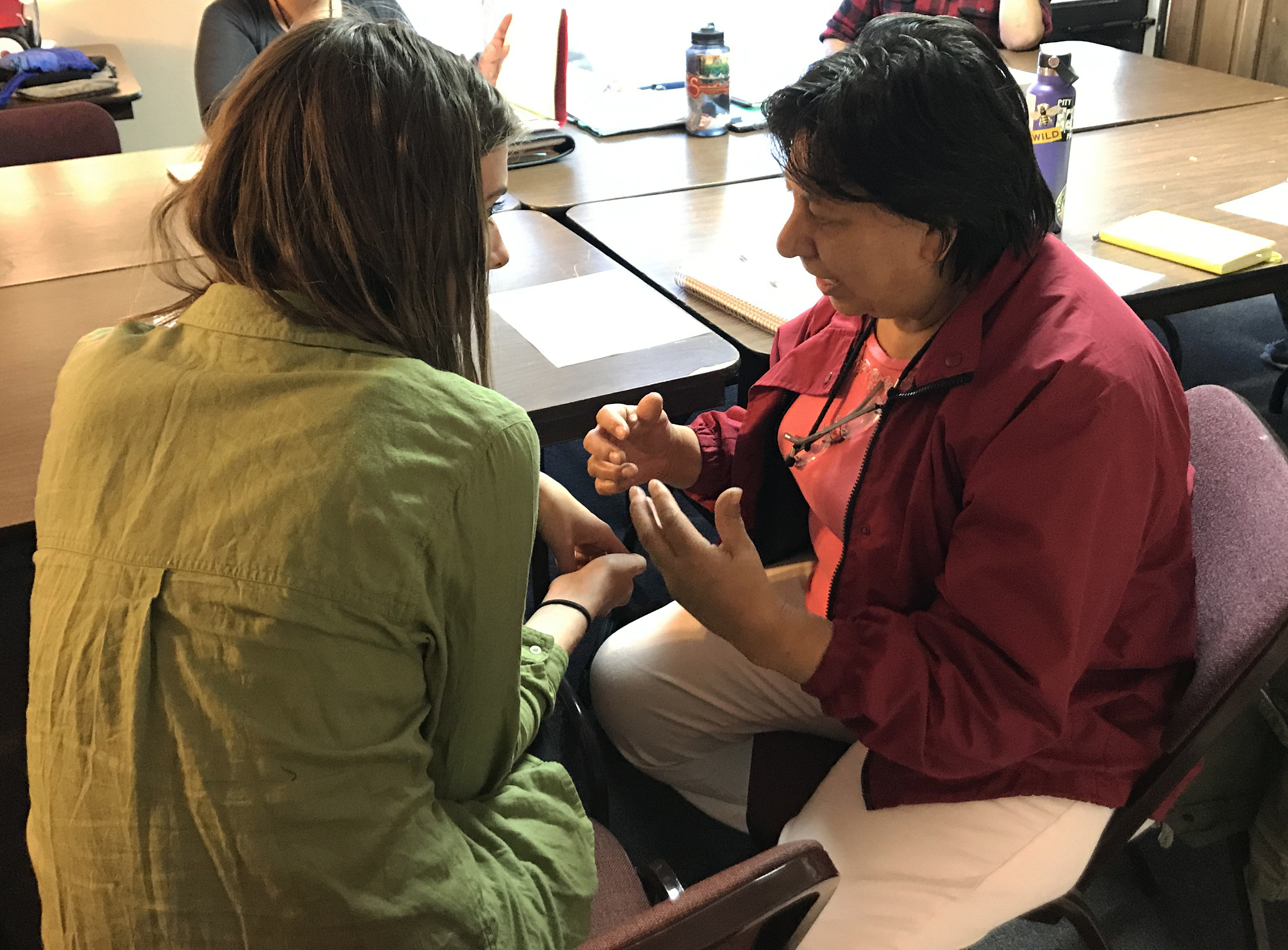 CUPI member Hannah Roberts speaks with NAIC leader Maria de Jesus Guillen at an NAIC immigration team meeting