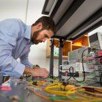 Ryan Behunin working in physics lab