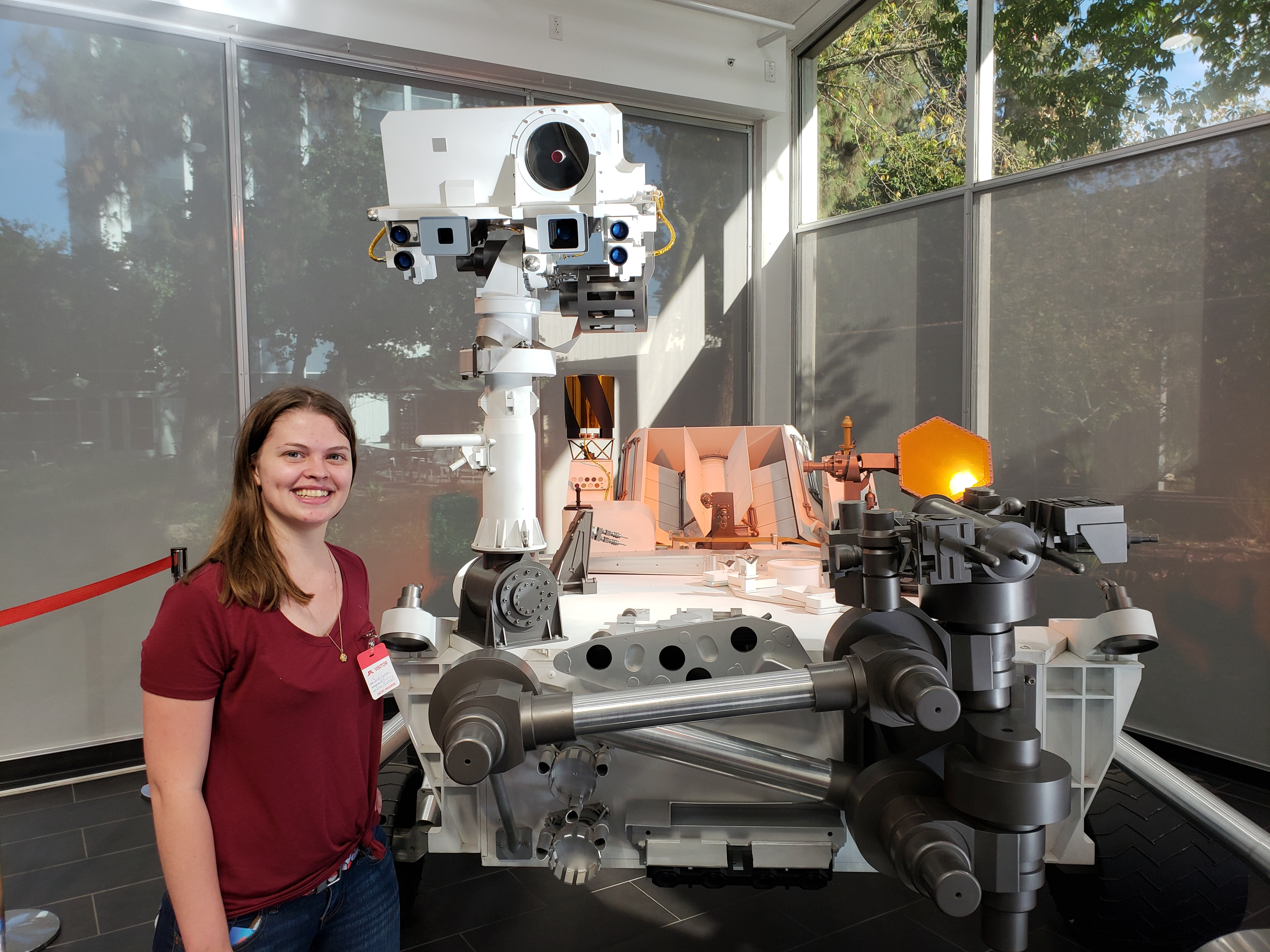 Lamm standing with replica model of Curiosity rover