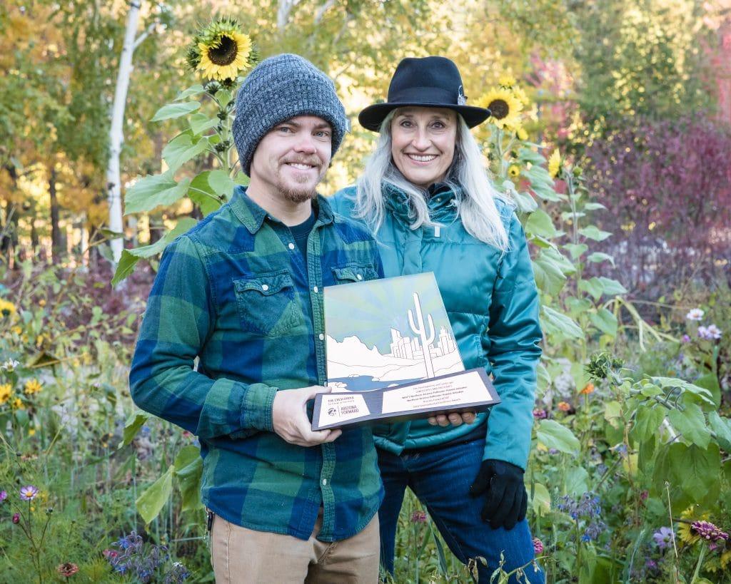 Tyler Linner (left) and Jocelyne Shiner of NAZPHI, standing among Autumn flowers in the SSLUG Garden on south campus.