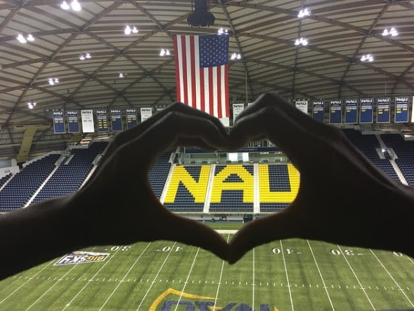 Hands make heart shape around NAU letters