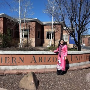 Visiting Fulbright scholar in front of NAU sign