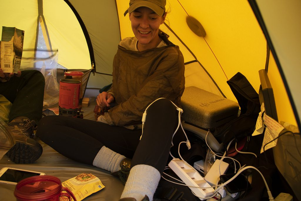 Katie Orndahl in a tent in the Arctic organizing remote sensing equipment