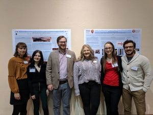 Chrissina Burke standing with Anthropology students in front of their research display
