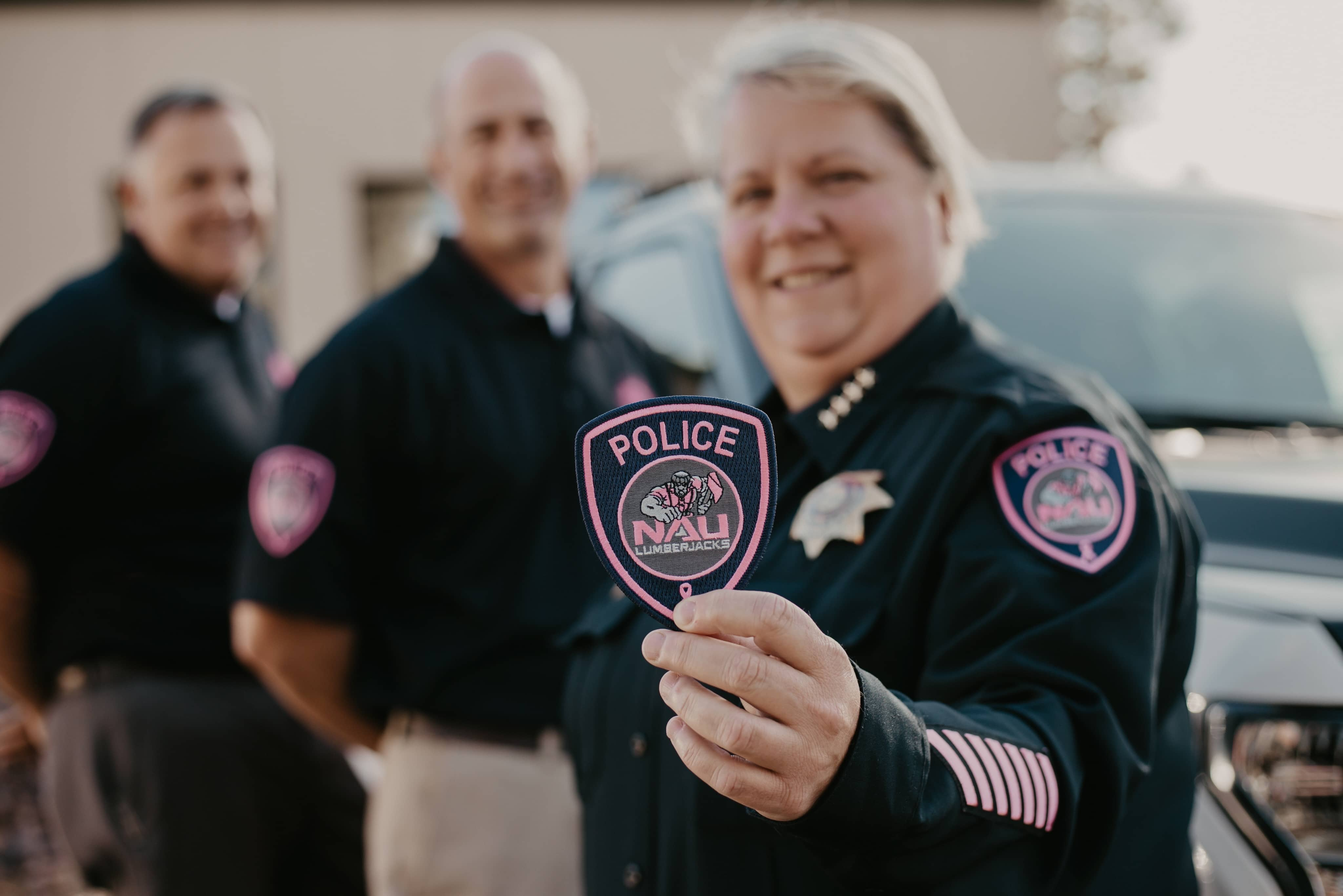 NAUPD officers hold pink patch