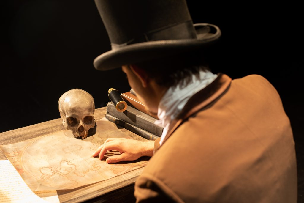 Dr. Frankenstein examines a map with a skull on it