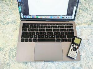 A handheld tape recorder sits on a laptop.