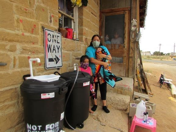 Hopi family stands with portable handwash stations