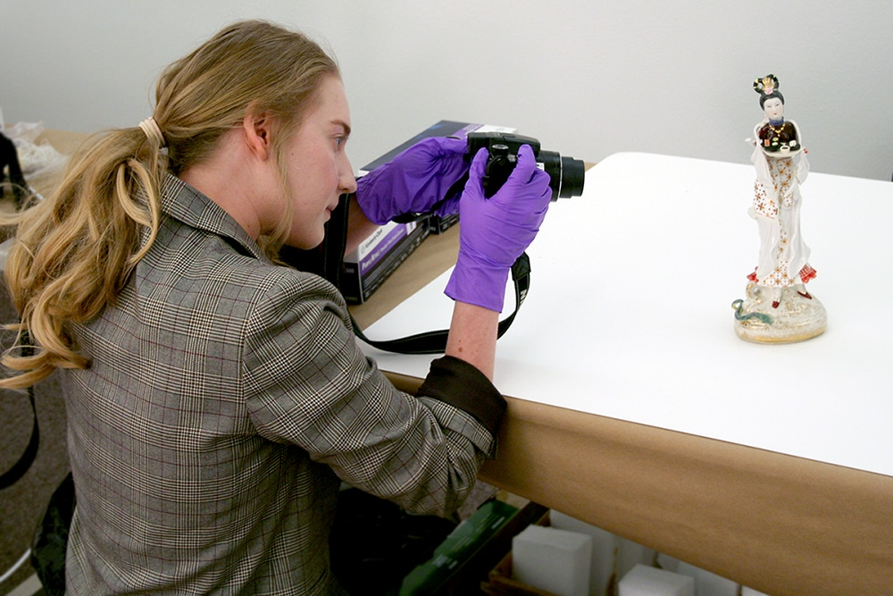 Student photographs a small artifact from the Macy collection