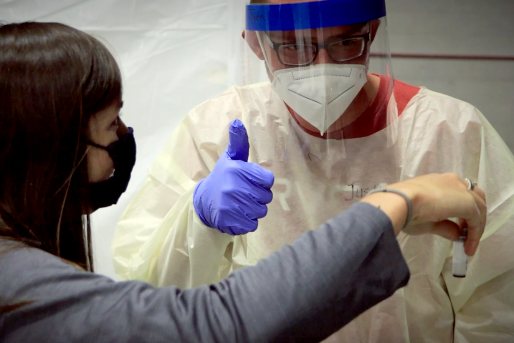 """Guy in PPE gives woman a """"thumbs up"""" for producing a good saliva sample"""