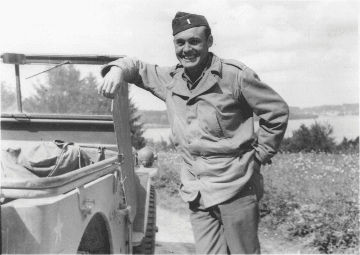 James P. Kuykendall leans against a military vehicle