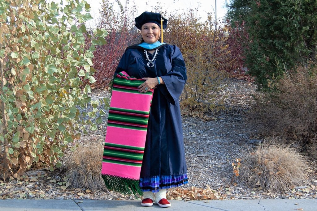 Esther Cadman in her commencement regalia and traditional Navajo dress