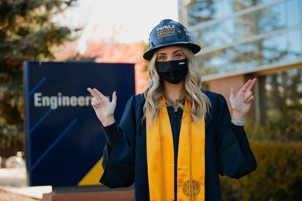 Construction management student in graduation gear with hard hat