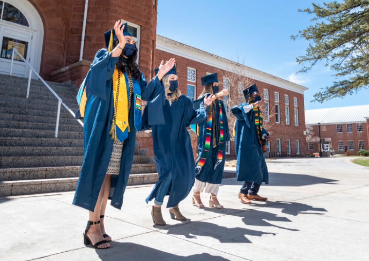 Graduates celebrating in front of old main
