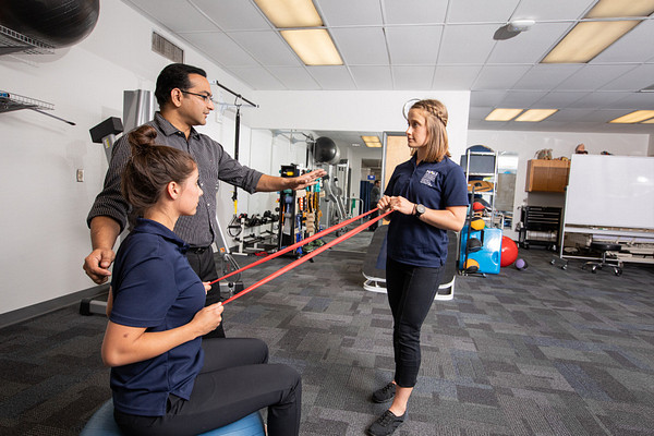 Physical therapy students practice exercises in a clinic.