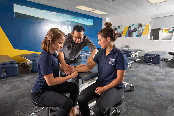 Physical therapy students practice exercises in a clinic as a professor helps.