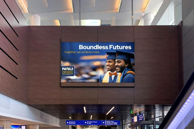Billboard with two men in graduation garb that says Boundless Futures together we achieve more