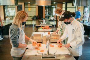 Volunteers chop food in the NAU test kitchen