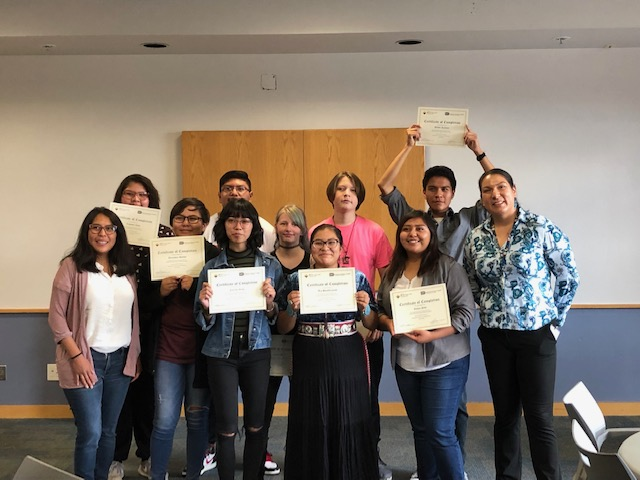 A group of students and their professors holding certificates