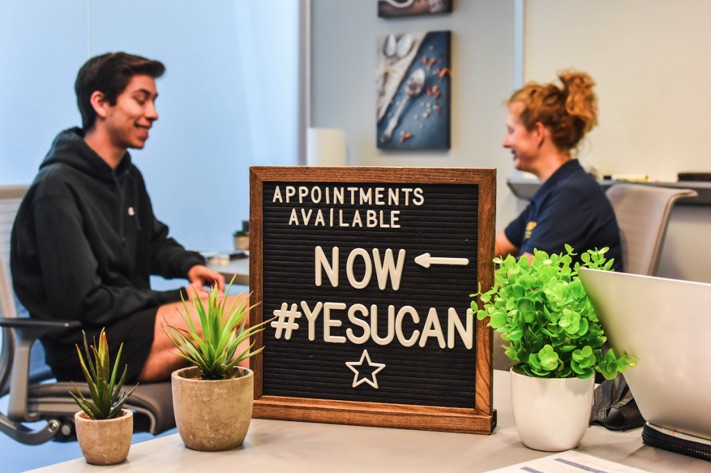 Student and health coach sitting behind a sign that says appointments available now #yesyoucan