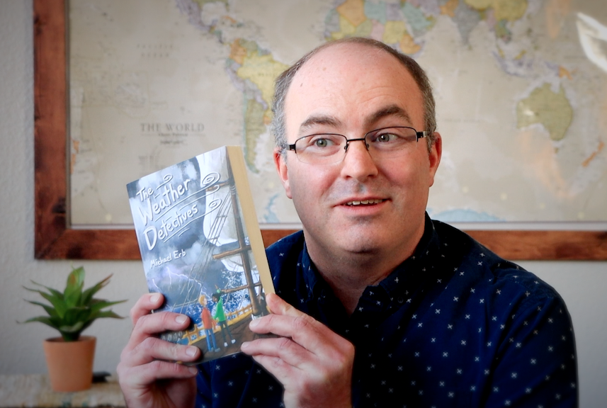 """Michael Erb holds up his book, """"The Weather Detectives"""""""