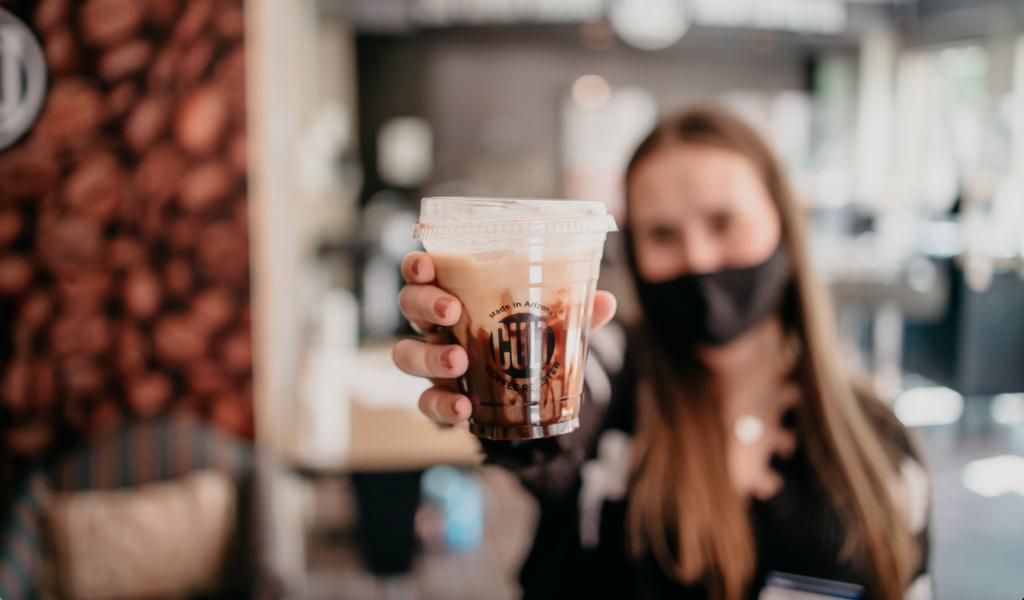 NAU student holds up coffee cup